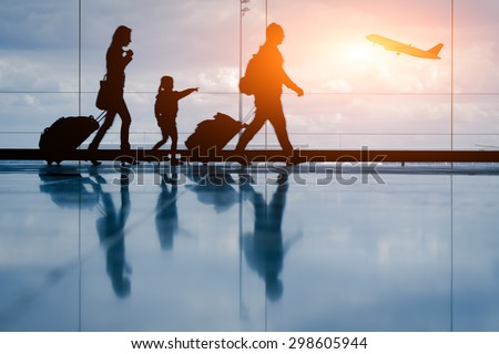 Silhouette of young family and airplane - stock photo