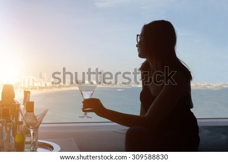 Silhouette of young girl holding a cocktail and sitting on the sofa in her suite hotel room while looking through big window a beautiful beach views - woman take a journey in luxury hotel with seaside - stock photo