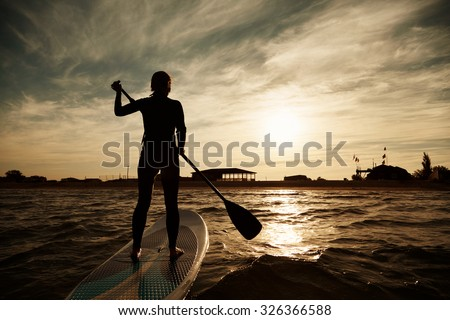 silhouette of young girl paddleboarding at sunset, recreation sport paddling ocean beach surf orange sunlight reflection hue on water - stock photo