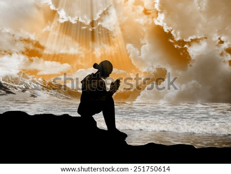 Silhouette of young girl praying to god  - stock photo
