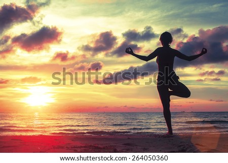Silhouette of young girl standing at yoga pose on the beach during an amazing sunset. - stock photo