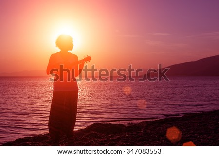 Silhouette of young girl standing on the beach with ukulele, at the sunset against the sun