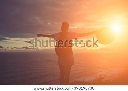 Silhouette of young girl with hat looking far away at sunset on a beach (intentional sun glare and vintage color) - stock photo