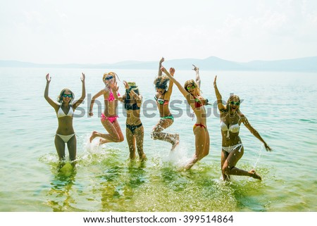 Silhouette of young group of people jumping in ocean at sunset. Team of adult girl jump in water on summer beach against blue sky with clouds Water splash Hair fly in air. Empty space for inscription - stock photo