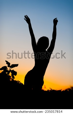Silhouette of young happy fit woman dancing on sunset - stock photo