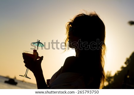 silhouette of young happy woman enjoying summer beach vacation at sunset sky background - stock photo