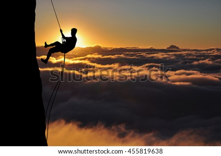 Silhouette of young man abseiling down from a cliff high above clouds and mountains, sun, beautiful colorful sky and clouds behind. Climber rappelling from a rock during sunset.