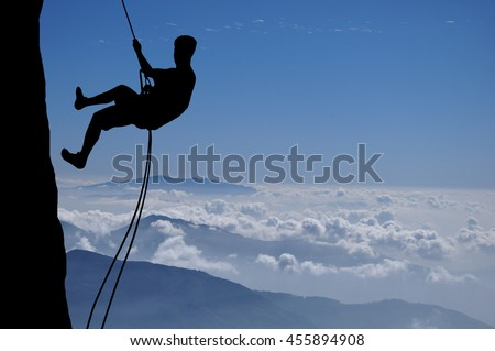 Silhouette of young man abseiling down from a cliff high above clouds and mountains, sun, beautiful colorful sky and clouds behind. Climber rappelling from a rock.