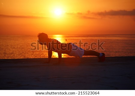Silhouette of young man at cross-training during colorful sunrise on the beach, athletic runner with muscular body doing some push ups outdoors, fitness and healthy lifestyle concept - stock photo