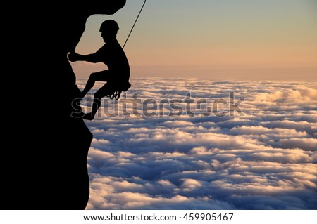 Silhouette of young man climbing on overhanging cliff high above clouds and mountains, sun, beautiful colorful sky and clouds behind. Climber hanging on rock and rope.