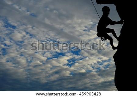 Silhouette of young man climbing on overhanging cliff, sun, beautiful colorful sky and clouds behind. Climber hanging on rock and rope.