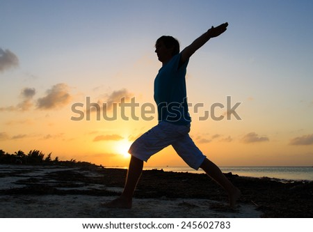 Silhouette of young man doing yoga at sunset beach