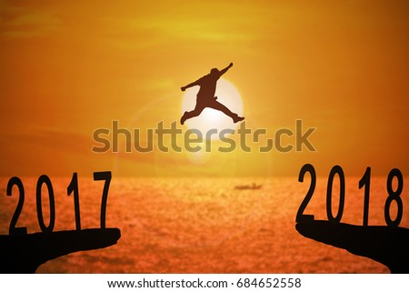 Silhouette of young man jumping between 2017 and 2018 years with beautiful sunset at the sea-concepts of news year and business target.