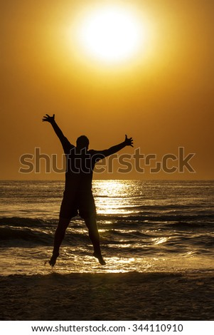 Silhouette of young man jumping on the beach to embrace the Sun