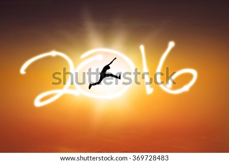 Silhouette of young man jumping on the sky while celebrating new year 2016 at sunset time