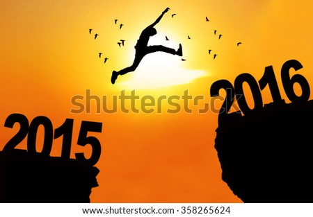 Silhouette of young man jumping over a cliff with numbers 2015 and 2016 at sunset time - stock photo