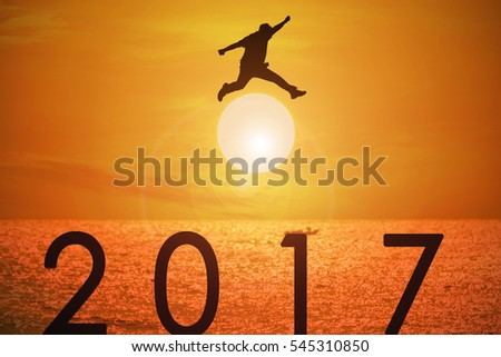 Silhouette of young man jumping over the numbers 2017 years with beautiful sunset at the sea.