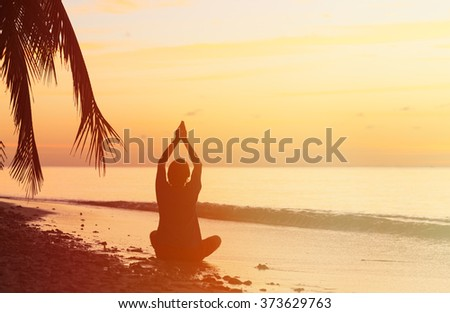 Silhouette of young man meditating at sunset