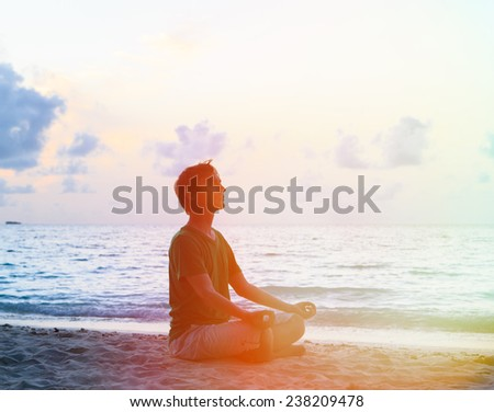 Silhouette of young man meditating at sunset beach - stock photo
