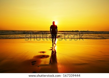 Silhouette of young man on the beach at sunset.  - stock photo