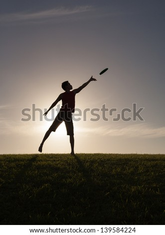 Silhouette of young man playing frisbee - stock photo