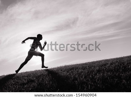 Silhouette of young man running - stock photo