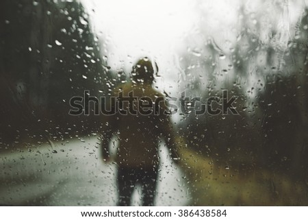 Silhouette of young man shot from a car, on a rainy day - stock photo