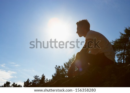 Silhouette Of Young Man Sitting On Rock