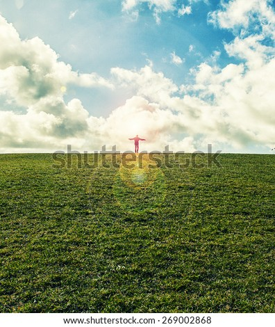 Silhouette of young man standing  with hands open wide on the top ofgreen field under sunset skies  ,freedom , success and freedom concept - stock photo