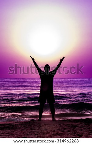 Silhouette of young man standing with open arms holding sphere of energy at sea