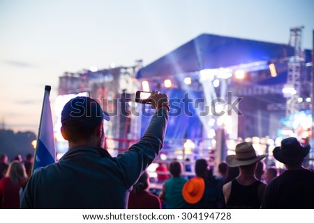 silhouette of young man; taking photo rock concert on the phone, open fest - stock photo