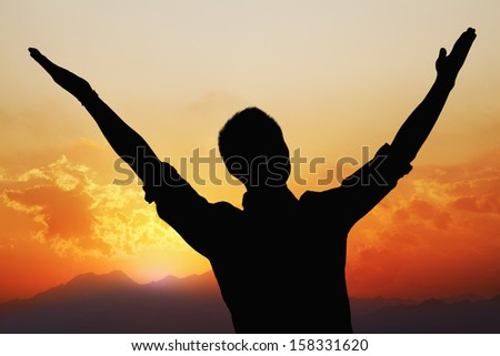 Silhouette of young man with arms raised with beautiful sunset and landscape in background