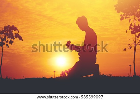 Silhouette of young musician holding a guitar on sunset.