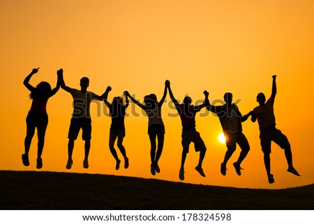 Silhouette of Young People Jumping at Sunset
