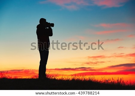 Silhouette of young photographer is enjoying sun. Photographer with mirror camera is ready to take sunrise pictures.  - stock photo