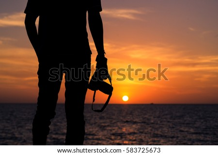 Silhouette of young photographer on the beach. Sunset Time