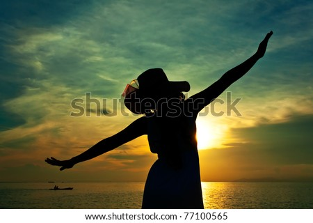Silhouette of young pretty woman with hat during sunset - stock photo