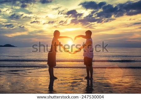 Silhouette of young romantic couple during tropical vacation, holding hands in heart shape on the ocean beach during sunset. Love story. Romantic wedding couple.  - stock photo