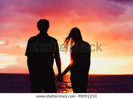 Silhouette of Young Romantic Couple Holding Hands at Sunset - stock photo