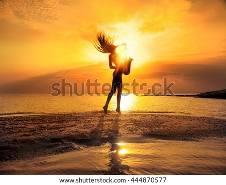 Silhouette of young sexy woman playing saxophone on the beach at sunset