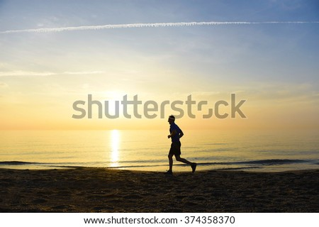 silhouette of young sport man running outdoors on beach at golden color sunset with orange and purple sky in front of the sea in fitness and healthy lifestyle concept