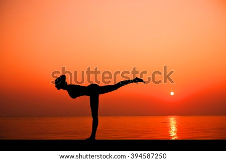 Silhouette of young sport woman practicing yoga on the beach at sunset.