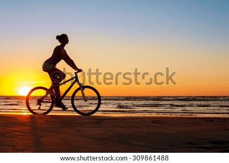 Silhouette of young sporty woman riding bicycle on the sunset  background on the beach. Summertime multicolored outdoors horizontal image. - stock photo