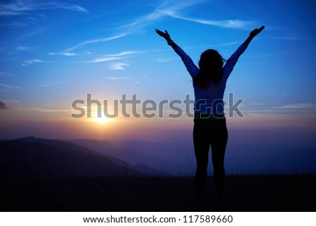 Silhouette of young woman against sunset with blue sky - stock photo