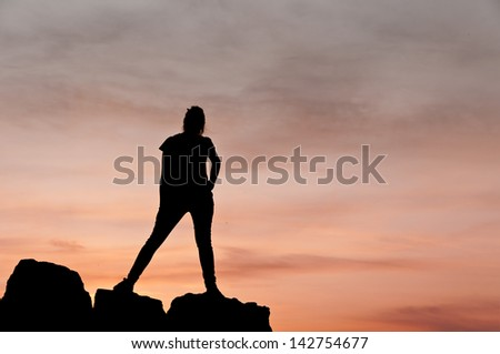 Silhouette of young woman dancing on a few rocks at the sunset - Horizontal