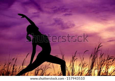 Silhouette of young woman doing yoga at outdoor park. - stock photo