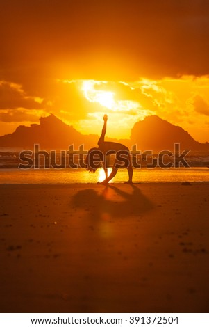 Silhouette of young woman doing yoga on the beach touching her toes