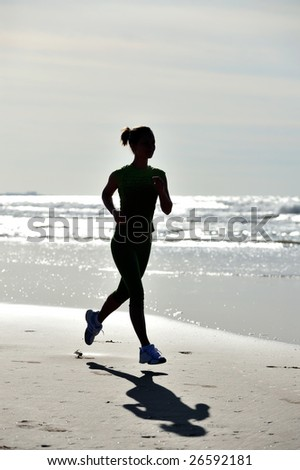 silhouette of young woman jogging on the beach - stock photo
