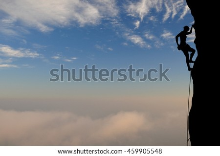 Silhouette of young woman lead climbing high above clouds and mountains, sun, colorful sky and clouds behind. Climber on top rope, hanging on rock and putting hand to chalk bag with powder magnesium.