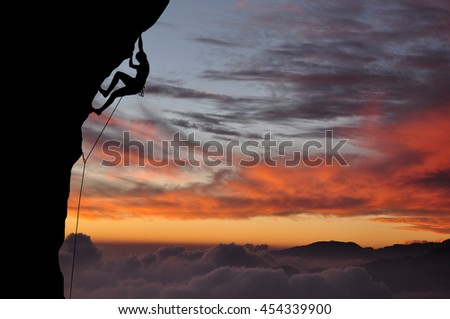 Silhouette of young woman lead climbing on overhanging cliff high above clouds and mountains, sun, beautiful colorful sky and clouds behind. Climber on top rope, hanging on rock during sunset. - stock photo